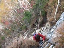 Средн-достигший возраста hiker взбираясь вверх лестница стоковое изображение