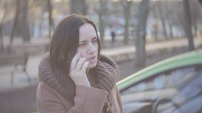 Средн-постаретая женщина говоря на телефоне около автомобиля акции видеоматериалы
