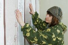 Средн-постаретая женщина клеит обои стоковые фотографии rf