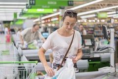 Средн-постаретая женщина на проверке в супермаркете Женщина рассчитывать проверку в супермаркете стоковое изображение rf