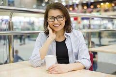 Средн-постаретая женщина на таблице с чашкой кофе Стоковые Фото