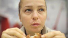 Средн-постаретая кавказская женщина есть жареную курицу в кафе фаст-фуда акции видеоматериалы