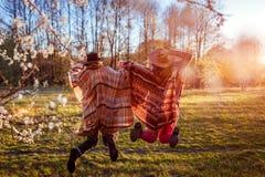 Средн-постаретая мать и ее взрослая дочь скача в зацветая сад Принципиальная схема дня ` s матери потеха имея женщин Стоковые Фотографии RF
