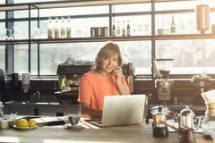 Средн-постаретое barista женщины работая на компьтер-книжке и говоря на smartphone Стоковое Фото