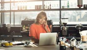 Средн-постаретое barista женщины работая на компьтер-книжке и говоря на smartphone Стоковые Фотографии RF