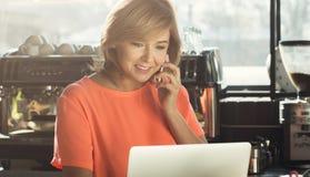 Средн-постаретое barista женщины работая на компьтер-книжке и говоря на smartphone Стоковая Фотография