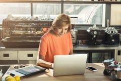 Средн-постаретое barista женщины работая на компьтер-книжке Стоковое фото RF