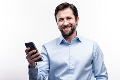 Средн-постаретый бородатый человек представляя с его сотовым телефоном Стоковые Фотографии RF