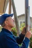 Средн-постаретый построитель человека в синем пиджаке и голубой крышке устанавливает штендер черного листового железа на уровне стоковые фотографии rf
