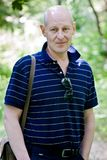 Средн-постаретый человек идет в парк лета стоковые изображения