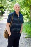 Средн-постаретый человек идет в парк лета стоковые фотографии rf