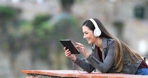 Средства массовой информации женщины наблюдая и слушая в планшете видеоматериал