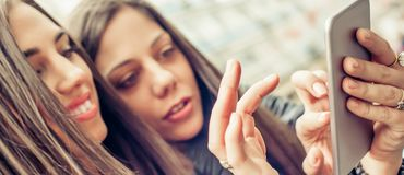 2 средства массовой информации интернета подруг счастливых наблюдая социальных в smartph стоковая фотография