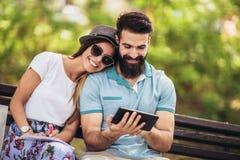 Средства массовой информации пар наблюдая в цифровой таблице на открытом воздухе стоковая фотография rf