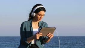 Средства массовой информации счастливой женщины наблюдая и слушая на планшете видеоматериал