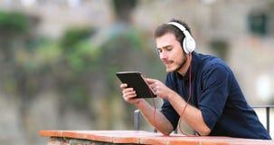 Средства массовой информации человека наблюдая и слушая на планшете акции видеоматериалы