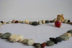 Среди камешков, ангел с красным сердцем в его руках Стоковые Изображения