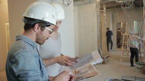 Среди ремонтов, 2 люд в шлемах обсуждают проект на безопасностях видеоматериал