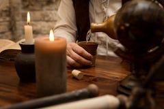 Средневековая таблица, человек льет вне питье Стоковые Фотографии RF