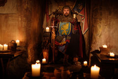 Средневековый король на троне в старом интерьере замка Стоковые Фотографии RF