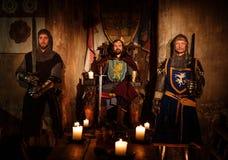 Средневековый король с его рыцарями в старом интерьере замка Стоковые Изображения RF