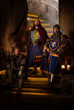 Средневековый король с его рыцарями в старом интерьере замка стоковое изображение