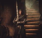 Средневековый рыцарь в старом интерьере замка Стоковые Фотографии RF