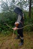 Средневековый лучник стороны стоит с черным hoodie и с напряженной кривой и с стрелкой Стоковое Изображение RF