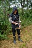Средневековый лучник с черным клобуком и покрашенными стрелками в колчане стоит с стрелкой Стоковые Изображения
