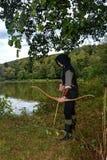 Средневековый лучник с черным клобуком стоит с напряженными кривой и стрелкой на воде Стоковая Фотография