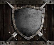 Средневековый экран рыцаря и пересеченные шпаги дальше Стоковая Фотография