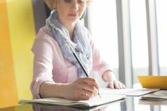 Среднее взрослое сочинительство коммерсантки на блокноте на столе в офисе Стоковое фото RF