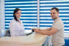 Среднее работник службы рисепшн взрослой женщины получая карточку от пациента в клинике дантиста Стоковые Фото