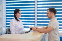 Среднее работник службы рисепшн взрослой женщины получая карточку от пациента в клинике дантиста Стоковая Фотография