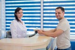 Среднее работник службы рисепшн взрослой женщины получая карточку от пациента в клинике дантиста Стоковое Изображение RF