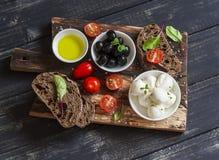 Среднеземноморская закуска - моццарелла, оливки, хлеб ciabatta рож, томаты вишни на деревенской деревянной разделочной доске Стоковые Фото