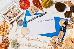 Среднеземноморская концепция с открыткой, солнечными очками и раковинами моря Стоковое Фото
