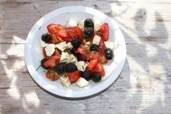Среднеземноморской салат на деревенской деревянной предпосылке Стоковые Изображения RF