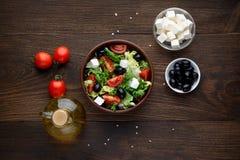 Среднеземноморской салат с оливками и фета в шаре на деревенском деревянном столе Стоковые Изображения RF