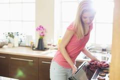 Средние печенья выпечки взрослой женщины в кухне Стоковая Фотография RF