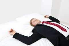 Средний взрослый бизнесмен спать в кровати дома Стоковые Изображения