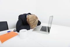 Средний взрослый бизнесмен спать компьтер-книжкой на столе в офисе Стоковое Изображение