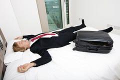 Средний взрослый бизнесмен с багажом спать в кровати дома Стоковое Фото
