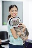 Средний кот нося взрослой женщины с конусом в клинике Стоковое Изображение RF