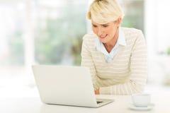 Средний портативный компьютер женщины времени Стоковые Фото