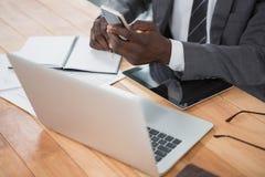 Средний раздел бизнесмена используя телефон и другие приборы мультимедиа Стоковая Фотография