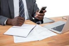 Средний раздел бизнесмена используя телефон и другие приборы мультимедиа Стоковое Фото