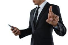 Средний раздел бизнесмена используя телефон пока касающся незримому интерфейсу Стоковые Изображения