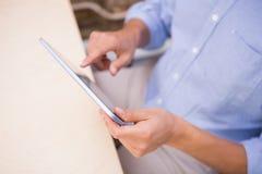Средний раздел бизнесмена используя цифровую таблетку на столе Стоковое фото RF