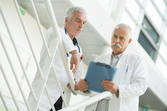 Средний раздел врачует обсуждать над доской сзажимом для бумаги в больнице Стоковые Изображения RF